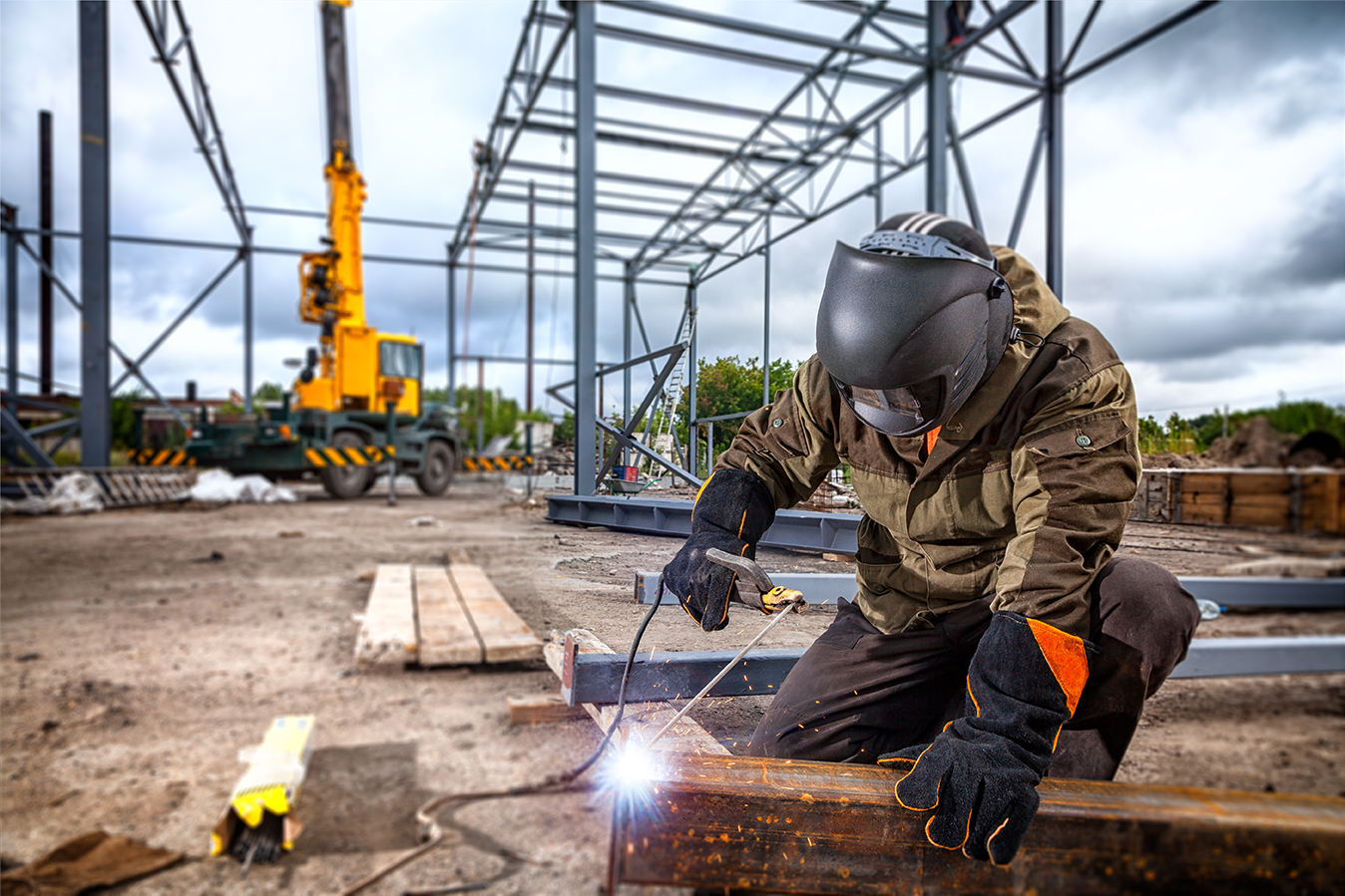 A young  man welder in brown uniform, welding mask and welders l